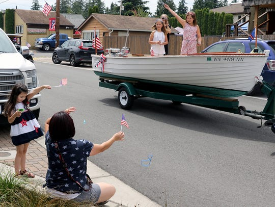 Sophia Dankovchik, 7, and her mom, Mirian, from Port Orchard, get candy and a bead necklace thrown to them during the Fourth of July Parade in Keyport on Wednesday. The event is a small-town community parade, with kids, dogs and bikes.