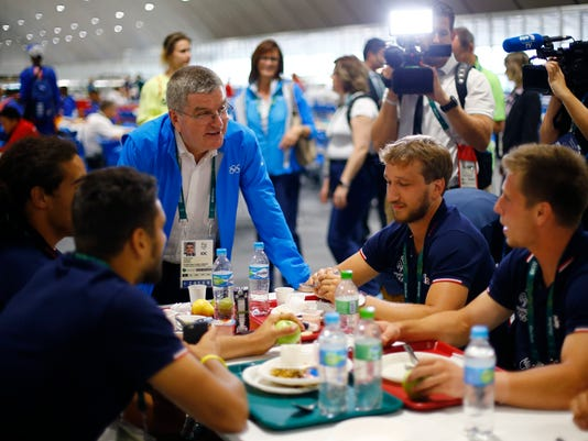 Tomas Bach, President of the International Olympic Committee, greets athletes in the dining hall after moving into the Olympic village in Rio de Janeiro, Brazil, July 28, 2016. (Ivan Alvarado/Pool Photo via AP)