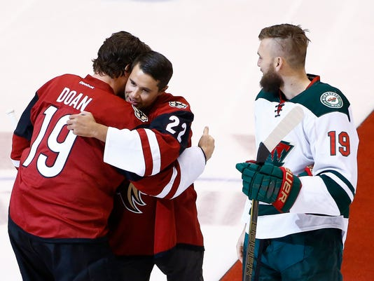 Craig Cunningham (22), the 26-year-old captain of the Tucson Roadrunners, the Arizona Coyotes' AHL affiliate, gets a hug from Coyotes team captain Shane Doan, left, after Cunningham dropped the puck in an opening ceremony as former Coyotes player and current Minnesota Wild player Martin Hanzal, right, looks on prior to an NHL hockey game Saturday, April 8, 2017, in Glendale, Ariz. Just five months ago Cunningham was fighting for his life after collapsing on the ice during pregame warmups. (AP Photo/Ross D. Franklin)