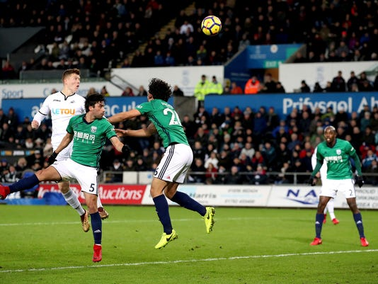 Swansea City's Alfie Mawson, left, heads the ball over the bar during their English Premier League soccer match against West Bromwich Albion at the Liberty Stadium, Swansea, Wales, Saturday, Dec. 9, 2017. (Nick Potts/PA via AP)