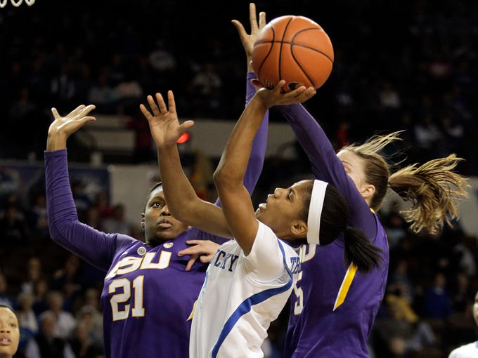 Kentucky's Janee Thompson, center, shoots under pressure from LSU's Shanece McKinney (21) and Jeanne Kenney, right, during the first half of an NCAA college basketball game on Sunday, Feb. 2, 2014, in Lexington, Ky. (AP Photo/James Crisp)