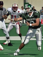 MSU quarterback Ryan Van Dyke pitches the ball as Wisconsin's