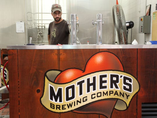 John Inmon cleans a kegerator at Mother's Brewing Company,