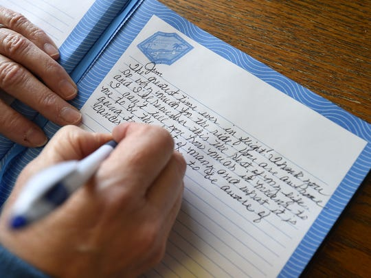 Breast cancer survivor Susan Payne, of Mountain Home, writes a personal note in Jim Davis' log book Monday after taking the first flight in his Passion Flights For Life tour.