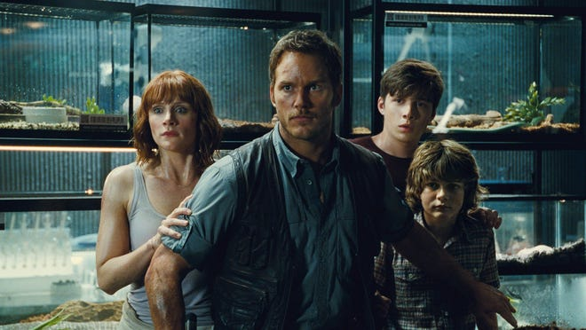 """This photo provided by Universal Pictures shows, Bryce Dallas Howard, from left, as Claire, Chris Pratt as Owen, Nick Robinson as Zach, and Ty Simpkins as Gray, in a scene from the film, """"Jurassic World,"""" directed by Colin Trevorrow, in the next installment of Steven Spielberg's groundbreaking """"Jurassic Park"""" series. The Universal Pictures 3D movie releases in theaters on June 12, 2015."""
