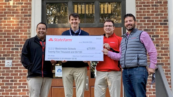 Westminster Schools of Augusta director of development Wesley Brown, second from left, stands with State Farm representatives in front of the school Wednesday, Nov. 18, holding a check for $25,000 towards Westminster's new robotics league as one of the winners of State Farm's Neighborhood Assist contest.