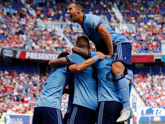 Former Saint Joseph High School star RJ Allen, top of pile, celebrates a goal scored by NYCFC teammate Ben Sweat against the New York Red Bulls.
