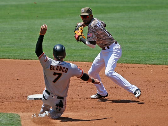 San Diego Padres shortstop Alexei Ramirez, right, prepares to release a relay to first base to complete a double play after forcing out San Francisco Giants' Gregor Blanco (7) in the second inning of a baseball game Sunday, July 17, 2016, in San Diego. (AP Photo/Lenny Ignelzi)