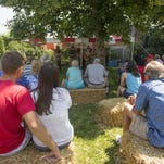 People sit on hay bales as the Bluegrass Patriots perform at Avery House Saturday, July 4, 2015. Though Monday brought a temporary cool-down for Fort Collins after a warm holiday weekend, temperatures will return to the upper 70s and mid-80s Tuesday.