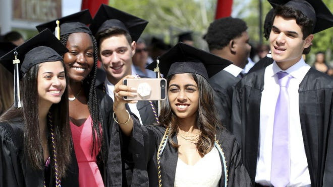 A group of Olympic Heights High Schools seniors pose before their graduation ceremony at the South Florida Fairgrounds in May 2018.