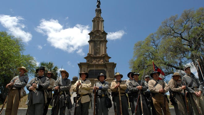 Civil War reenactors stand in front of the Confederate Monument in Forsyth Park on during a Confederate Memorial Day ceremony.