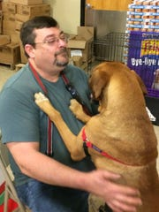 Chris Robinson, a volunteer foster parent with Augusta Dog Adoptions, holds his current foster dog, Jack, at an adoption event at the PetSmart in Waynesboro, Virginia, on Saturday, Dec. 24, 2016.