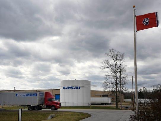 Trucks drive past the Kasai North America Inc. plant