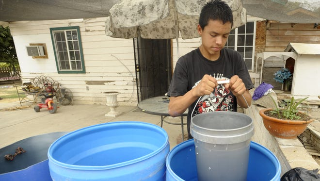 Luis Colunga, a resident of Monson, draws water out of 50-gallon barrels, due to their wells having gone dry in this 2014 file photo.