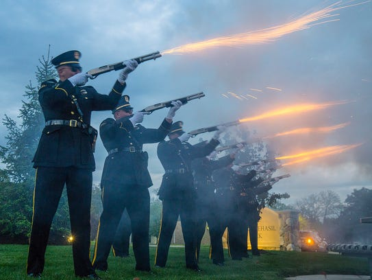 The Livonia Police Honor Guard fires a 3 volley salute.