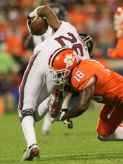 Clemson safety Jadar Johnson (18) tackles South Carolina