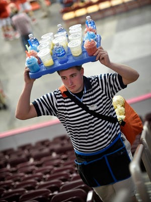 Craig Griffith Jr. walks the steps during the PIAA basketball championships selling drinks and popcorn.