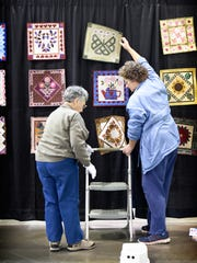 Anne Annibali and Donna Doberstein hang a flower block calendar at the Lebanon Expo Center in anticipation of the Lebanon Quilters Guild 11th Annual Exhibition of Quilts, Nov. 10 and 11.