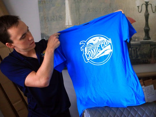 Ryan Romel displays a volunteer shirt for the first