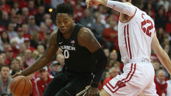 Xavier Musketeers guard Tyrique Jones (0) maneuvers around Wisconsin Badgers forward Ethan Happ (22) at the Kohl Center.