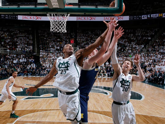 Michigan State's Xavier Tillman (23), Michigan's Moritz Wagner, center, and Michigan State's Matt McQuaid (20) reach for a rebound during the second half of an NCAA college basketball game, Saturday, Jan. 13, 2018, in East Lansing, Mich. Michigan won 82-72. (AP Photo/Al Goldis)