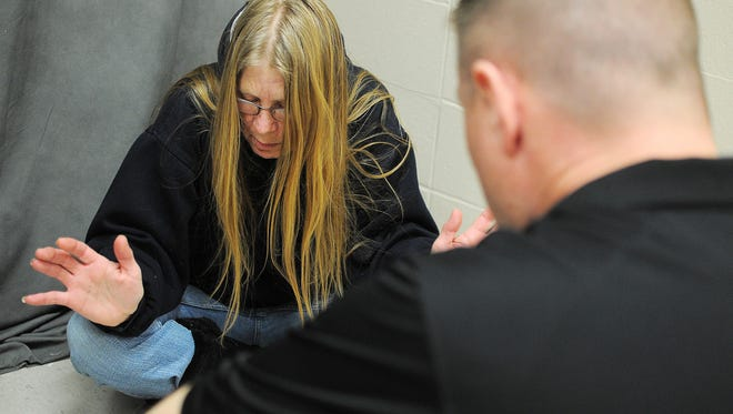 Officer Adam Petersen, with the Sioux Falls Police Department, speaks with Deb McClintock, an actor and community mental health therapist portraying a person suffering from depression and having issues getting medication, during a role playing exercise as part of a National Alliance on Mental Illness Crisis Intervention Training program on Thursday, Feb. 5, 2015, at the Law Enforcement Center in Sioux Falls, S.D. Law enforcement officers from the South Dakota Highway Patrol, Pierre, Aberdeen and the Sioux Falls Police Department took part in the training, which helps officers learn better ways to respond to a situation where person is having a mental health crisis.