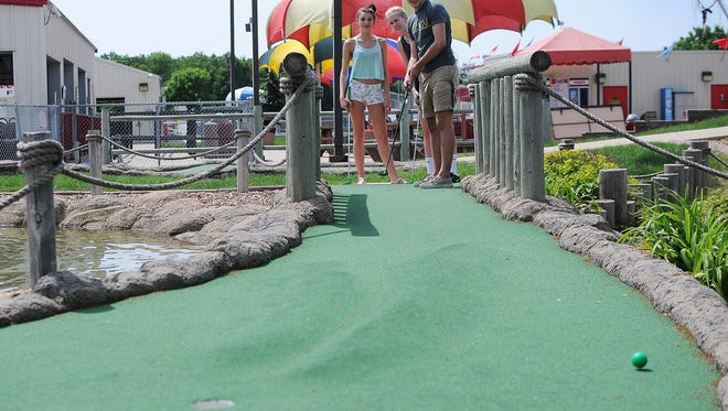 Evan Charlton, 17, of Navarre, Fla., hits his ball while playing miniature golf with Krista Lincoln, 17, of Sioux Falls, left, and his cousin Kara Wagner, also 17 and from Sioux Falls, on Thursday, June 4, 2015, at Thunder Road Family Fun Park in Sioux Falls. Lincoln said that her and Wagner decided to bring Charlton to play miniature golf because it was his last day in town.