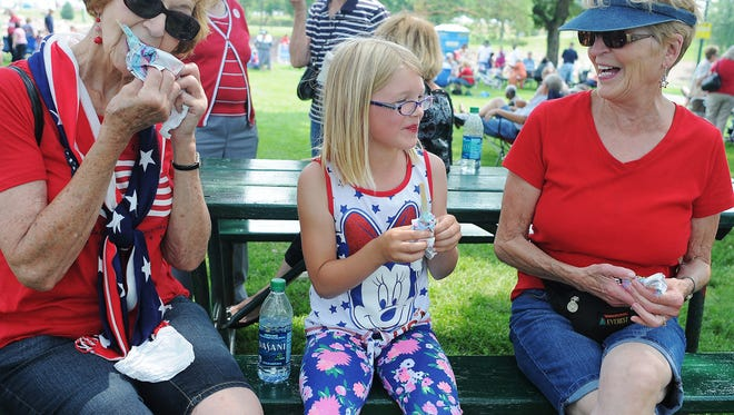 From left, Gracella Bultje of Brandon, S.D., Kari Patterson of Washburn, N.D., and Peg Patterson, also of Brandon, have ice cream treats during a picnic in the park as part of Sioux Falls' 4th of July Celebration on Saturday, July 4, 2015, at Falls Park in Sioux Falls.