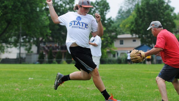 Nick Buysman, 15, of Sibley, Iowa, scores a run during the annual Phil Roof baseball game on Saturday, July 4, 2015, at Riverdale Park in Sioux Falls. The group gets together every year for the 4th of July to play baseball.
