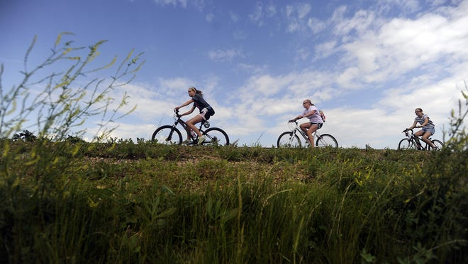 Riders cruise the bike path through near Granite City on Saturday, June 29, 2013.