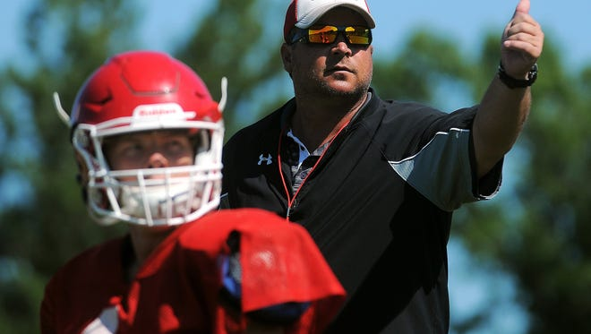 Lincoln head football coach Aaron Beavers talks to his team during a practice Thursday, Aug. 20, 2015, at Lincoln High School in Sioux Falls.