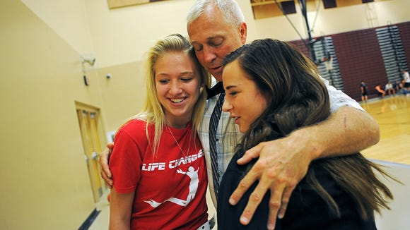 Kevin Lein, principal of Harrisburg High School, gets a hug from Mariah Spotanske, left, and Sophie Schoepf, both 14 and Harrisburg High School freshman, Friday, Oct. 2, 2015, at Harrisburg High School in Harrisburg, S.D., just days after he was shot.