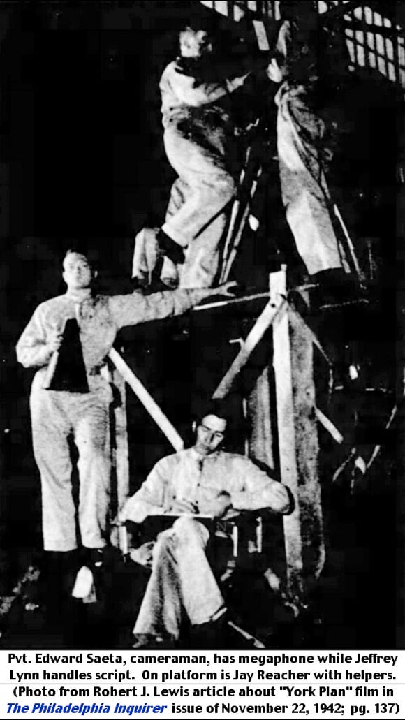 """Pvt. Edward Saeta, cameraman, has megaphone while Jeffrey Lynn handles script.  On platform is Jay Reacher with helpers. (Photo from Robert J. Lewis article about """"York Plan"""" film in The Philadelphia Inquirer, issue of November 22, 1942; page 137.)"""
