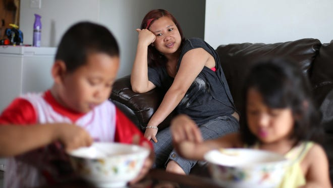 Sui Hlei Cuai watches her son, Filimon, and daughter, Gracy, eat dinner at their apartment in Des Moines. The children were returned to Cuai last spring after a child custody nightmare.