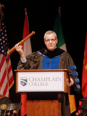 Champlain College President Donald Laackman holds a spyglass symbolizing the theme of his inauguration speech Saturday, which focused on a future of helping the college improve lives and Vermont's economy.