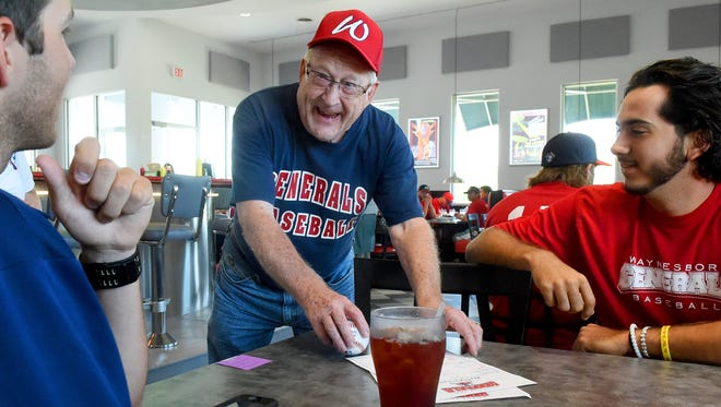 Lomar Milburn smiles as he brings his baseball over to a table with Waynesboro General's general manager Tyler Hoffman and pitcher Frankie Romano. Fans could meet and even have lunch with the team during a gathering at the Orbital Grill in Waynesboro Tuesday afternoon, June 16, 2015. Each year, Milburn gets the entire team to sign a baseball which he then adds to his collection.