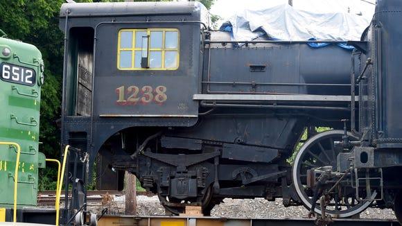 Steam locomotive 1238 sits loaded on a railroad flatcar.