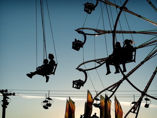Riders in bucket seats of several rides are silhouetted