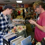 Zac Brown purchases vinyl albums from Revolver Records store owner, right, Eric Jones, during Record Store Day Saturday, a day when usually vintage albums are rereleased or new recording are made available through record stores.  Two Record Store Days take place each year, one in the spring and one in the fall.
