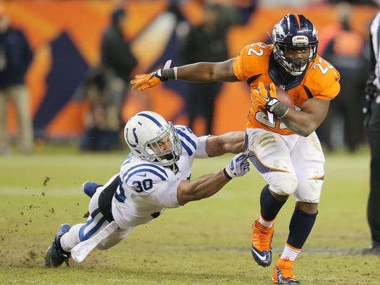 Indianapolis Colts free safety LaRon Landry can't get a handle on Denver Broncos running back C.J. Anderson who escaped on a big fourth and one in the third quarter. Indianapolis faced Denver in the NFL playoffs Sunday, January 11, 2015.