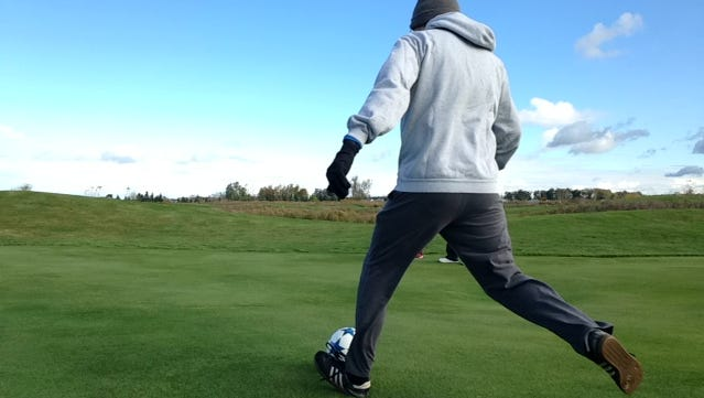 Patrick Harrison kicks the ball at the start of a hole at The Falcon FootGolf course in East Lansing Saturday, Oct. 17.