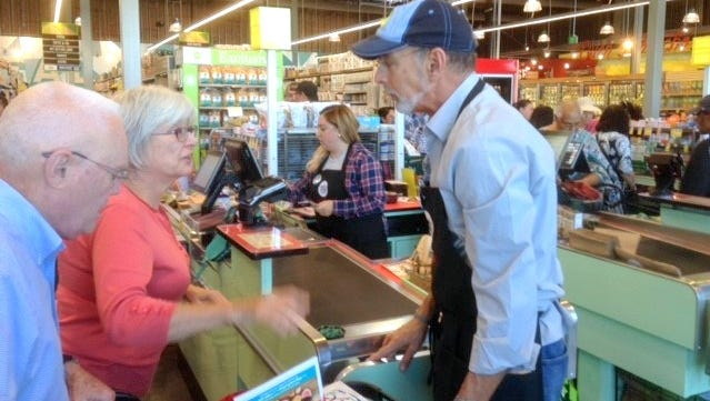 Mark Heins helps customers during the October opening of El Paso's first Whole Foods Market. Heins was fired as store manager late last month.