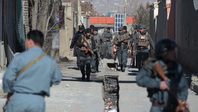 Afghan policemen keep watch following blasts at a Shiite cultural center in Kabul on Dec. 28, 2017.