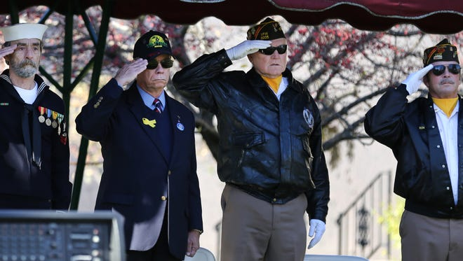 Veterans salute during the playing of Taps.