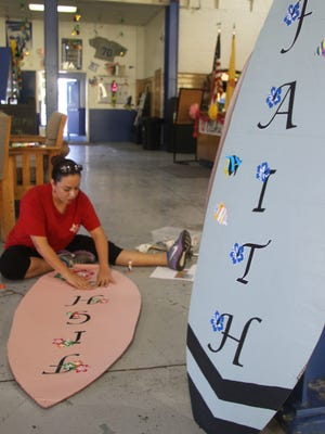 Elba Alanza, an employee at the Riverwalk Recreation Complex, decorates cardboard surfboards in preparation for Thursday's Paint the Town Pink kick off.
