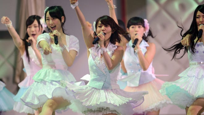 Yuko Oshima (C) and other AKB48 members perform on a stage prior to their 27th song selection, called the AKB48 General Election in Tokyo on June 6, 2012.