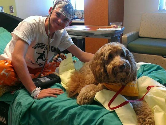 Nick Bezold poses with a seizure dog — trained to detect and deal with seizures in epilepsy patients.