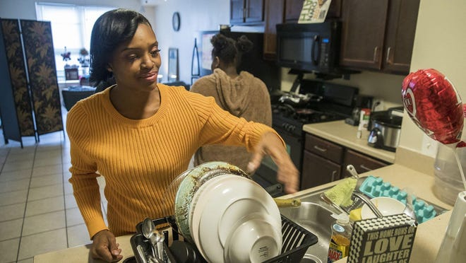 "LaChantia Anderson, 39, does the dishes in her apartment. She is trying to get into coding and creating apps and says, ""I just want a good job at a great company one day."" For the last four years, she has struggled with homelessness and being able to save up enough money to complete her coursework."