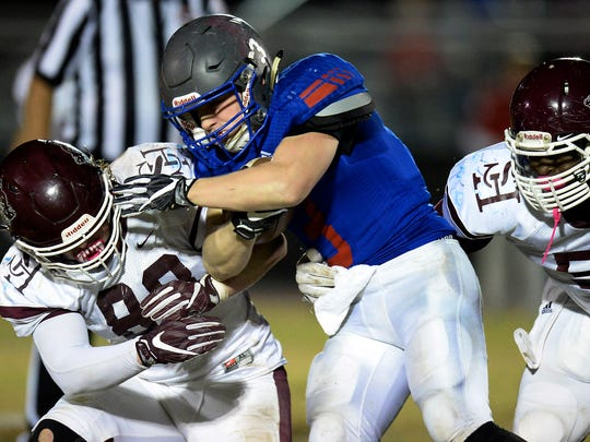 Page running back Donald Johnson, center, is tackled by Spring Hill linebacker Kennedy Ross (88) during the second half of an high school football playoff game on Friday, Nov. 11, 2016, in Franklin, Tenn. Spring Hill won 45-31.