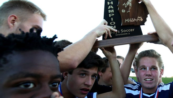 Mattawan celebrates with their championship trophy after defeating Dearborn Divine Child at the MHSAA Division 2 boys soccer finals at Stoney Creek High School in Rochester Hills, Michigan on Saturday, November 5, 2016.